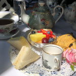 Finger sandwiches, currant scone and Fresh fruit garnished with a fresh rose, Perfect!
